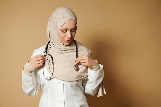 ヒジャーブを身に着け、首に電話内視鏡を置くイスラム教徒の女性医師の自信を持って肖像画 Premium写真