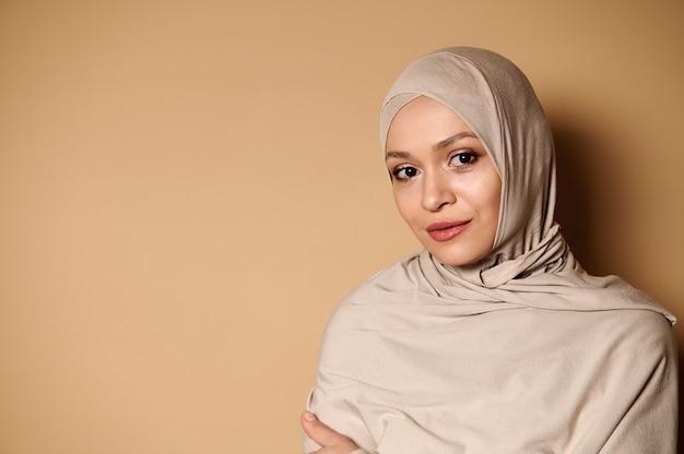 ヒジャーブと厳格な保守的な服装で穏やかで美しいアラブのイスラム教徒の女性の自信を持って肖像画。