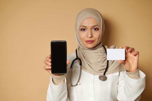 白いプラスチックの空白のカードとスマートフォンを保持し、それらを前面に表示するヒジャーブを身に着けている若いイスラム教徒の女性医師の自信を持って肖像画