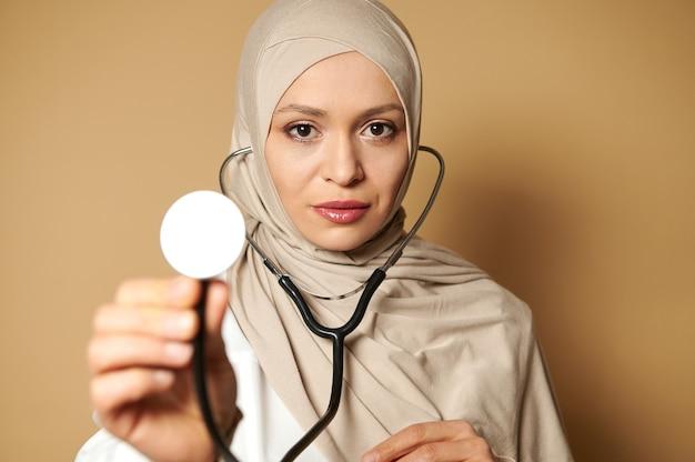 ヒジャーブを身に着け、聴診器を正面に見せているエレガントな女性のイスラム教徒の医師の自信を持って肖像画