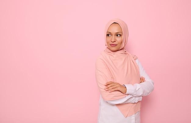 매력적인 시선과 분홍색 히잡으로 머리를 덮은 아랍 이슬람 아름다운 여성의 자신감 있는 초상화, 복사 공간이 있는 컬러 배경에 4분의 3 서서 복사 공간을 바라보고 있습니다.