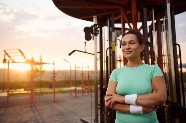 魅力的な混血、ゴージャスなヒスパニック系スポーツウーマン、日の出の朝に屋外ジムのマシンの背景に腕を組んで立っているスポーツウェアの女性アスリートの自信を持って肖像画