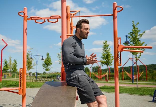 魅力的なスポーティな男、ハンサムなマッチョ、夏の屋外スポーツグラウンドでクロスバーやジムのマシンの背景にスポーツウェアのヨーロッパの白人の筋肉ビルドアスリートの自信を持って肖像画