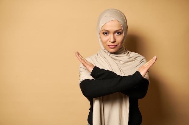 否定を示すために彼女の腕を交差させるヒジャーブで覆われた頭を持つイスラム教徒の女性の自信を持って肖像画