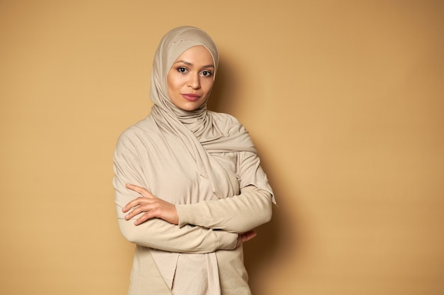 コピースペースとベージュの表面に腕を組んでポーズをとる穏やかで成功した美しいアラブのイスラム教徒の女性の自信を持って肖像画