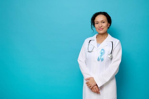 青い意識リボン、世界糖尿病デーのシンボル、コピースペースで青い色の背景に対してポーズをとってカメラを見て微笑む白い医療用ガウンの女医の自信を持って肖像画