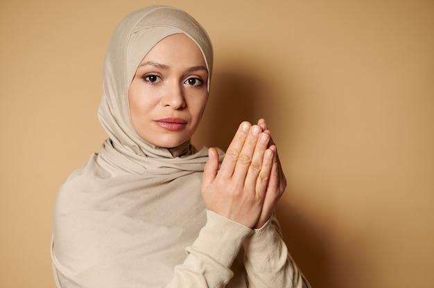 ベージュのヒジャーブとナマズを祈る伝統的な服を着ている若い穏やかなイスラム教徒の女性の自信を持って肖像画
