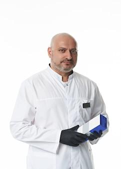 Уверенный портрет на белом красивого мужчины-врача, пластического хирурга в черных перчатках