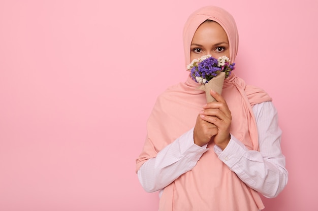 Confident portrait of young charming arab muslim woman in pink hijab with beautiful dark eyes, attractive gaze, looking at camera, covers half of her face and mouth with a craft bouquet of flowers