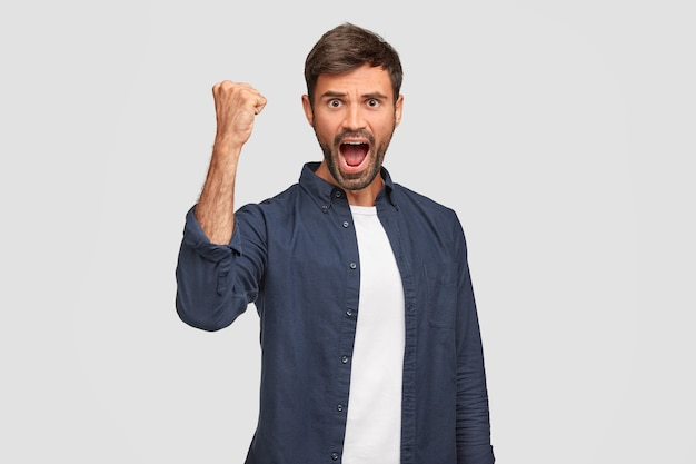 Confident positive male winner keeps hand raised clenched in fist, has widely opened mouth, exclaims with triumph, being emotional, feels success, stands against white wall. achievement concept