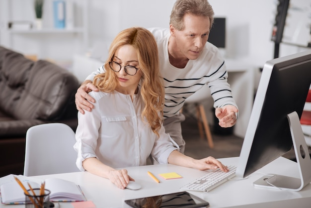 Confident positive playful boss standing in the office while working and hugging the secretary