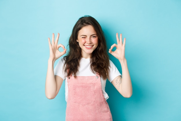 Confident and positive young woman winking and smiling, showing okay signs in approval, say yes, give approval, praise good work, standing against blue background.