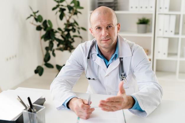 Уверенный практикующий врач со стетоскопом и ручкой смотрит на вас, давая медицинский совет в больнице