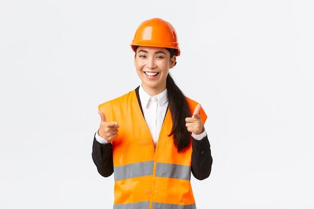 安全ヘルメットと反射ジャケットの自信を持ってかなりアジアの女性建設マネージャー、良い選択、良い仕事またはよくやった、立っている白い背景を賞賛するカメラに指を向ける