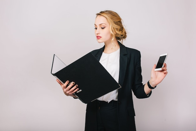 Confident pretty blonde businesswoman in office suit looking at folder in hands, holding phone. being busy, worker, secretary, executive, successful