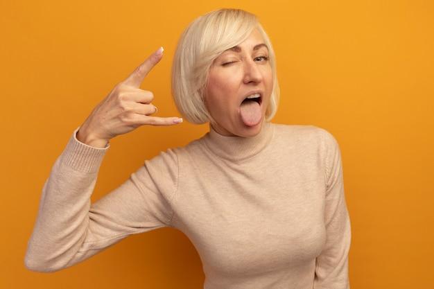 Уверенная в себе симпатичная славянская блондинка моргает и высунула язык, жестикулируя рогами, знак рукой на оранжевом