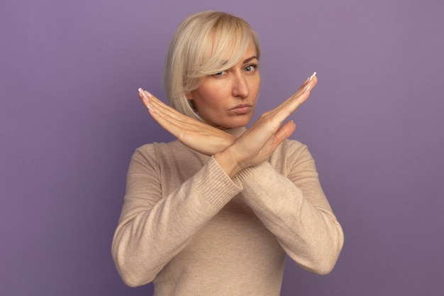 Confident pretty blonde slavic woman crossing hands gesturing no sign on purple