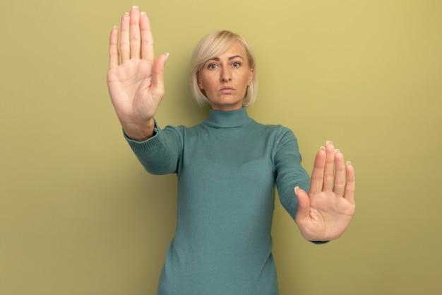 Уверенная красивая блондинка славянская женщина жестами останавливает знак рукой с двумя руками, изолированными на оливково-зеленой стене