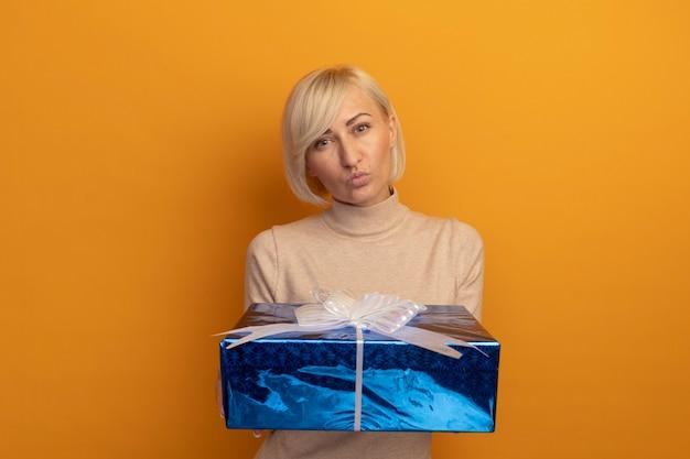 自信を持ってきれいな金髪のスラブ女性はオレンジ色の壁に隔離のギフトボックスを保持します
