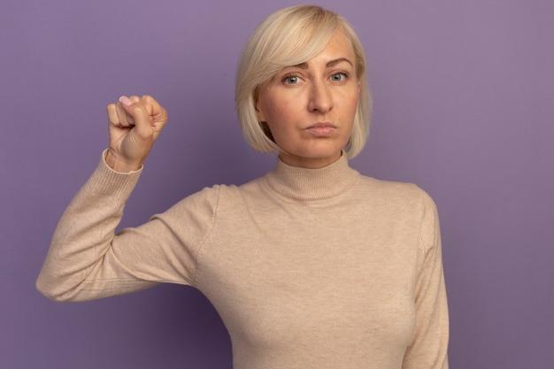 自信を持ってかなり金髪のスラブ女性は紫に拳を保ちます