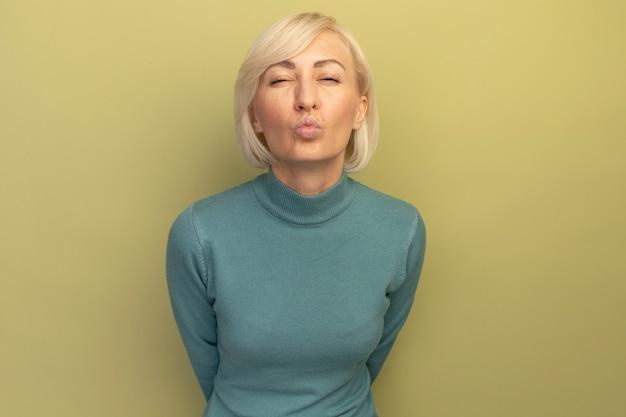 自信を持ってきれいな金髪のスラブ女性は、オリーブグリーンのカメラを見てキスをするふりをします