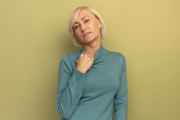 자신감이 예쁜 금발의 슬라브 여자가 올리브 그린에 칼라를 당깁니다.