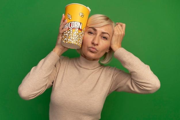 自信を持ってきれいな金髪のスラブ女性が頭に手を置き、緑の壁に分離されたポップコーンのバケツを保持します。