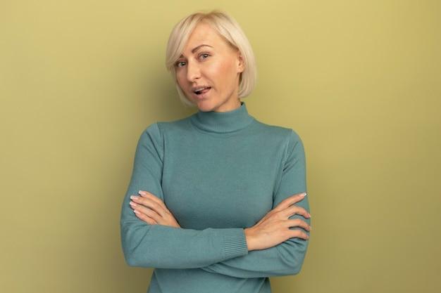 Уверенная в себе симпатичная славянская блондинка стоит со скрещенными руками, глядя в камеру на оливково-зеленом