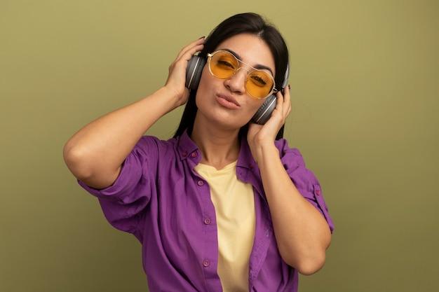 Fiduciosa ragazza caucasica abbastanza mora in occhiali da sole con le cuffie esamina la macchina fotografica su verde oliva