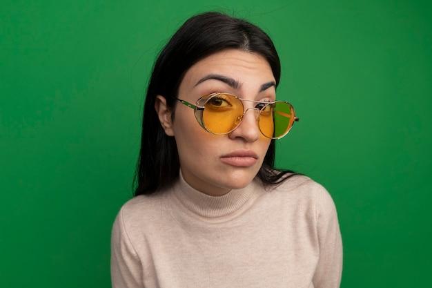 La donna abbastanza castana sicura in occhiali da sole esamina la parte anteriore isolata sulla parete verde