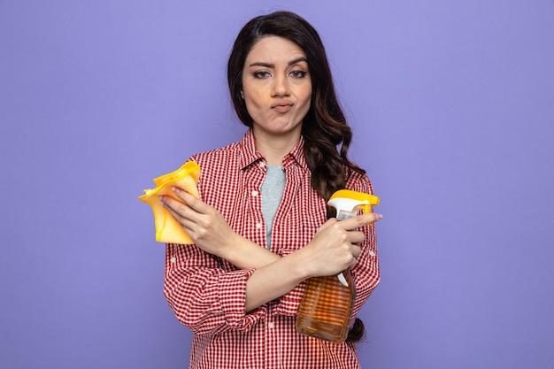 Fiduciosa donna abbastanza caucasica delle pulizie che tiene in mano panni per la pulizia e detergente spray e incrocia le mani