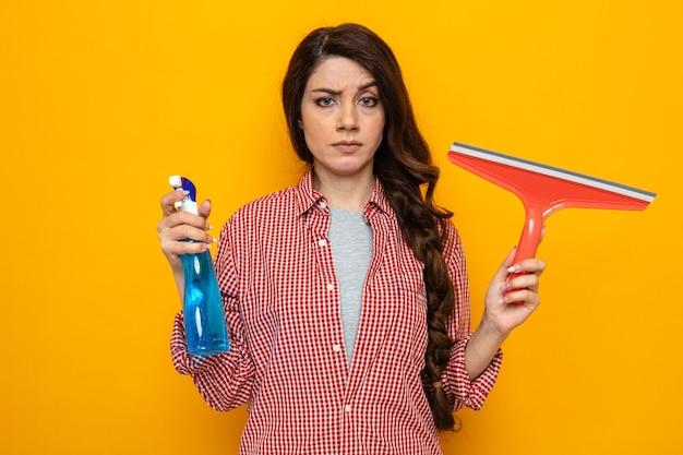 Уверенная, симпатичная кавказская уборщица, держащая ракель и спрей-очиститель и смотрящая вперед