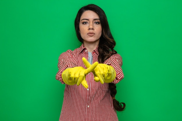 Confident pretty caucasian cleaner woman with rubber gloves crossing her fingers gesturing no sign