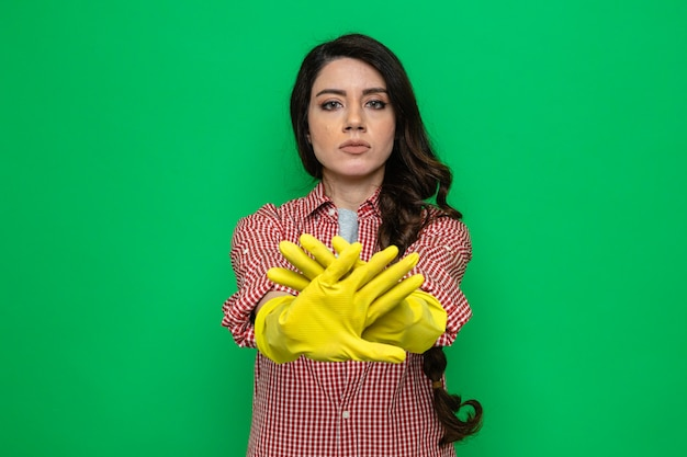 Confident pretty caucasian cleaner woman with rubber gloves crossing her hands gesturing stop sign