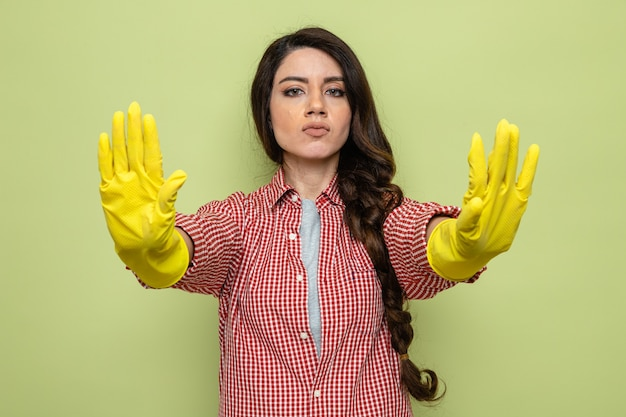 Confident pretty caucasian cleaner woman with rubber gloves gesturing stop sign with two hands and looking at front