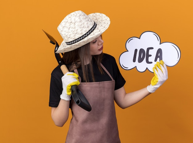원예용 모자와 장갑을 끼고 삽을 들고 주황색 벽에 복사 공간이 있는 아이디어 거품을 바라보는 자신감 있는 백인 여성 정원사