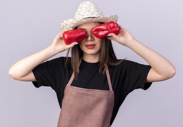 Уверенная красивая кавказская женщина-садовник в садовой шляпе, закрывающая глаза красным перцем на белом