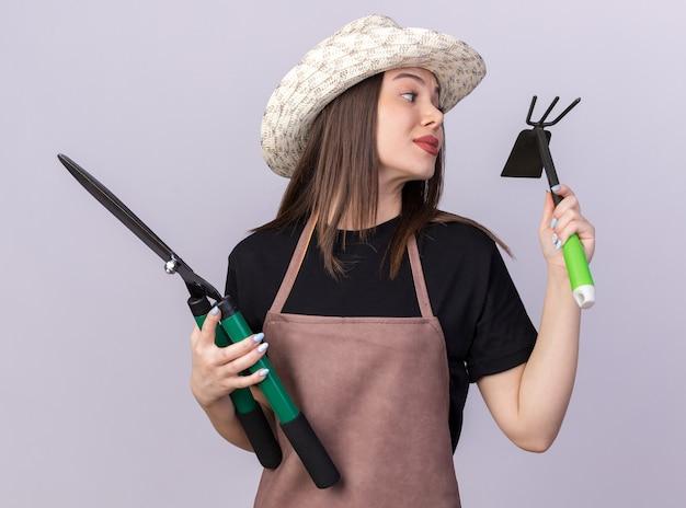 원예용 가위를 들고 원예용 모자를 쓰고 복사 공간이 있는 흰 벽에 격리된 괭이 갈퀴를 바라보는 자신감 있는 백인 여성 정원사