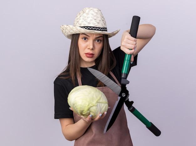 Giardiniere femminile abbastanza caucasico fiducioso che indossa cappello da giardinaggio che tiene forbici da giardinaggio e cavolo isolato sul muro bianco con spazio di copia