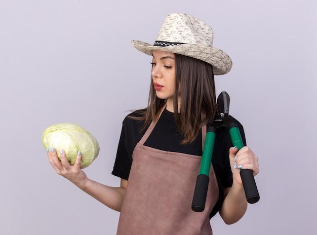 Giardiniere femminile abbastanza caucasico fiducioso che indossa cappello da giardinaggio che tiene forbici da giardinaggio e guarda il cavolo isolato sul muro bianco con spazio di copia