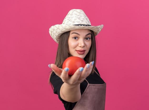 Giardiniere femminile abbastanza caucasico sicuro che porta il cappello di giardinaggio che tiene fuori il pomodoro sul colore rosa