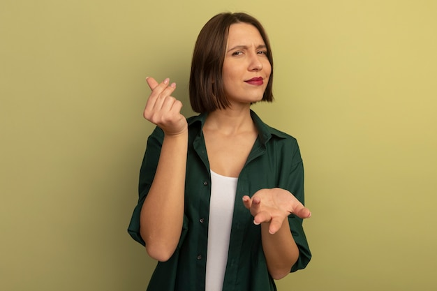 La donna abbastanza caucasica sicura tiene la mano aperta e gesti il segno della mano dei soldi su verde oliva
