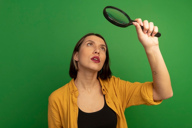 Confident pretty caucasian woman holds and looks at magnifying glass isolated