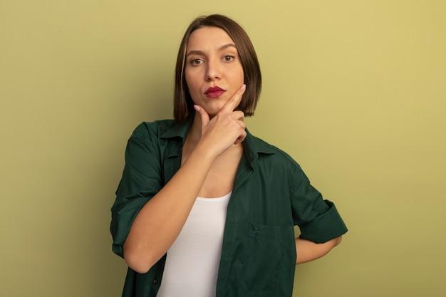 자신감이 예쁜 백인 여자는 올리브 그린에 턱에 손을 넣습니다