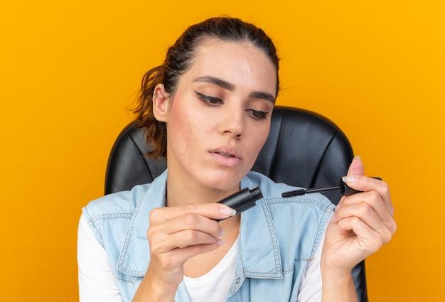 コピースペースとオレンジ色の壁に分離されたマスカラを保持し、見ている化粧ツールでテーブルに座っている自信を持ってかなり白人女性