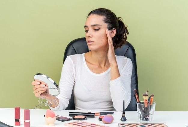 コピースペースのあるオリーブグリーンの壁に隔離されたミラーを保持し、見ている化粧ツールでテーブルに座っている自信を持ってかなり白人女性