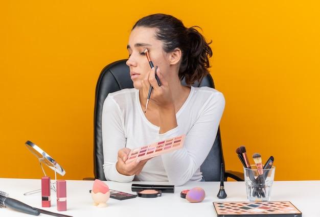 アイシャドウパレットを保持し、コピースペースでオレンジ色の壁に分離されたミラーを見て化粧ブラシでアイシャドウを適用してテーブルに座っている自信を持ってかなり白人女性