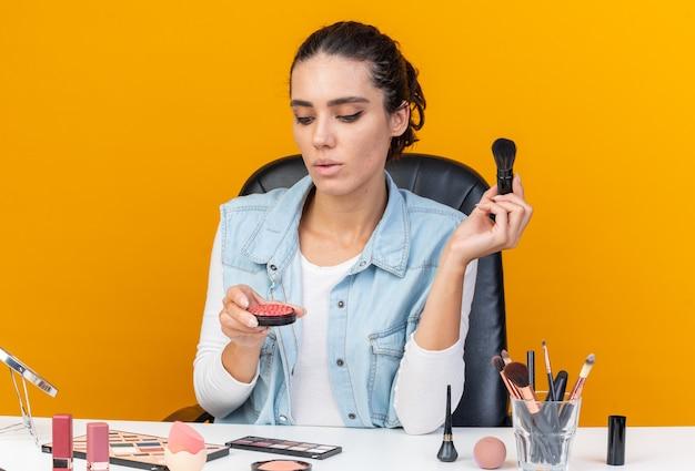 메이크업 브러쉬를 들고 주황색 벽에 격리된 홍당무를 보고 복사 공간이 있는 화장 도구를 들고 테이블에 앉아 있는 자신감 있는 백인 여성