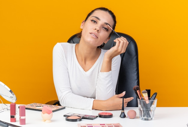 Confident pretty caucasian woman sitting at table with makeup tools applying eyeshadow with makeup brush