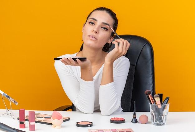 Donna abbastanza caucasica sicura che si siede al tavolo con strumenti per il trucco tenendo la tavolozza dell'ombretto e applicando l'ombretto con il pennello per il trucco isolato sulla parete arancione con lo spazio della copia